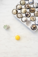 Yolk and shell quail eggs on the marble surface and cardboard box eggs