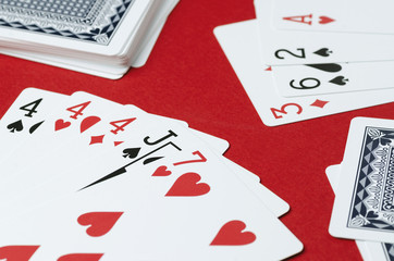 Playing cards on a red background. Combination in poker, three of a Kind