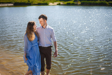 pregnant girl with curly long hair in beautiful blue dress and handsome young man hugging and walking on water along river shore, holding hands together, happy family concept