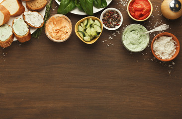 Assortment of bruschetta toppings on wooden kitchen table, top view