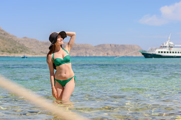 Frontal portrait of a young woman brunette in a green swimsuit standing in the emerald sea water and a hand holding a hat, copy space