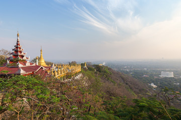 Panoramic view of pavilions and golden pagodas at the Mandalay Hill and the city below in Mandalay, Myanmar (Burma) on a sunny day.