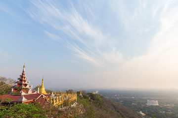 Panoramic view of pavilions and golden pagodas at the Mandalay Hill and the city below in Mandalay, Myanmar (Burma) on a sunny day. Copy space.