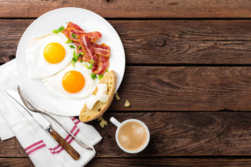 Fried eggs, bacon and italian ciabatta bread on white plate. Cup of coffee. Breakfast. Top view. Wooden background