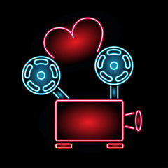 Neon sign movie for lovers. Love of cinema. Film projector with ribbon in the form of a heart. Neon sign for the cinema. Web banner