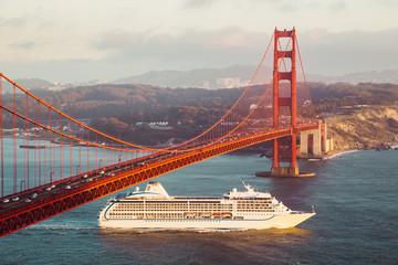 Wall Mural - Golden Gate Bridge with cruise ship at sunset, San Francisco, California, USA