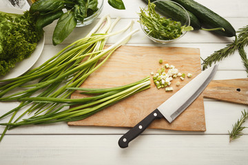 Cutting spring onion for fresh salad top view