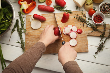 Woman cutting fresh radish on wooden board