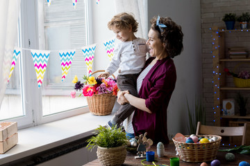 Portrait of pretty young mother holding little boy standing by window and laughing happily while celebrating Easter at home, copy space
