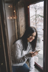 Beautiful brunette woman sitting next to window with mobile phone.
