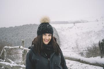 Pretty woman with hat posing in snowy landscape.