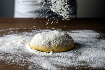 Raw dough ball sprinkled with white flour on a wooden table. Dynamically frozen flour in flight