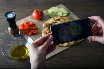 Female blogger taking pictures of cooked food with their hands, vegetable crackers, cooking blog, side light
