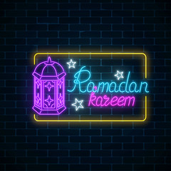 Glowing neon banner of ramadan islamic holy month on dark brick wall background. Ramadan kareem.