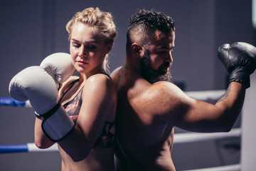 Boxing lessons concept. woman and man hold hands up in boxing gloves back to back