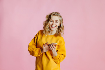 portrait of cheerful  caucasian female with curly blonde hair, poses on a pink background. woman looks for information on the Internet and looks through the websites by means of the smartphone.