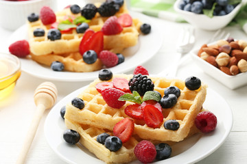 Sweet waffle with berries on white wooden table
