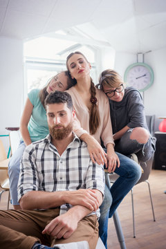 Funny group portrait of four sad or sleepy young people suffering of depression or workplace demotivation during work in a co-working office space