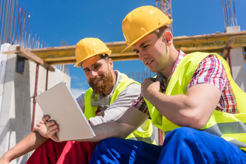 Side view of two workers reading online information or watching a video on a tablet PC, during break at work on the construction site of a contemporary building