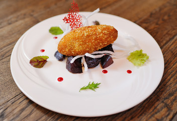 appetizing cutlet in battered beetroot on a white plate