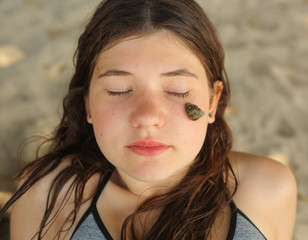 close up teen girl face photo with snail on her cheek natural skin care