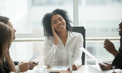 Absent-minded distracted black businesswoman dreaming of success and happiness at corporate group meeting, dreamy smiling african female boss thinking of new idea avoiding work stress lost in thought