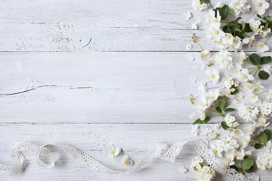 White wooden background with white spring flowers and lace ribbon