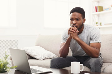 Thoughtful young african-american man at home