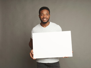 Picture of young african-american man holding white blank board