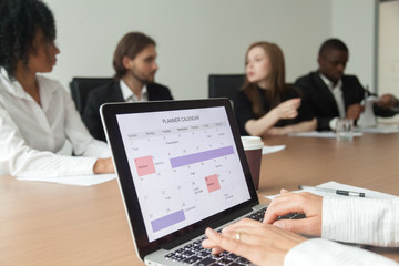 Woman using digital organizer or calendar application on laptop screen, businesswoman making events schedule with planner at office team meeting, time management and planning concept, close up view