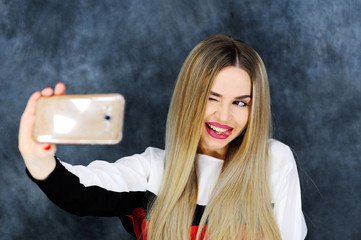 cute girl admires her white teeth filming themselves on the smartphone