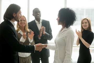 Grateful boss handshaking promoting african businesswoman congratulating with career achievement while colleagues applauding cheering successful worker, appreciation handshake, employee recognition Fotobehang