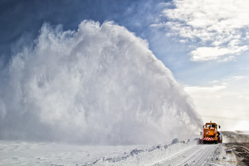 Snow-covered road cleaning by snow removal machine.