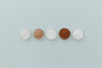 Baking soda, powder, cocoa, sugar, flour, yeast on cup for baking on pastel background. Minimal Flat lay