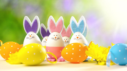 Cute Easter bunny ornaments and Easter Eggs on white table against garden background with lens flare.