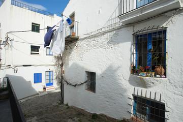 une ruelle avec des pavés au milieu des maisons à façades blanches et volet bleus