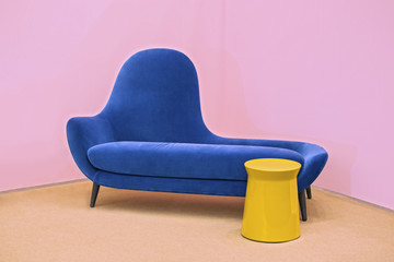 Navy blue sofa on a pink background, laconic interior