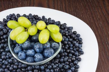 Blueberries and bunch of grapes on brown table. Vaccinium myrtillus. Close-up of white plate with luscious fresh berry fruits and glass bowl on wooden background.