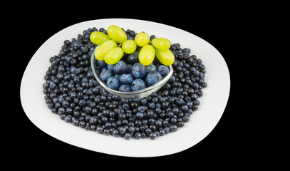 Organic blueberries and bunch of grapes. Vaccinium myrtillus. Small and big berry fruits on white plate and in glass bowl. Isolated on black background.