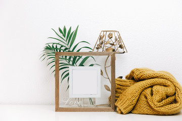 Minimal Mock up wooden frame with green tropical leaves and trendy warm sweater. Nordic decorations, Scandinavian style interior