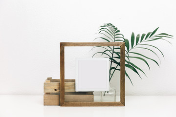 Mock up wooden frame with green tropical leaves. Nordic decorations, Scandinavian interior