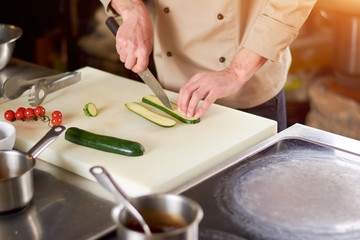 The process of cutting zucchini by chef. The chef in restaurant slicing green marrow on white cutting board. Preparation of dish.
