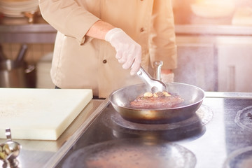 Chef frying meat with garlic. Hands of male chef frying duck breast at professional kitchen. Man at restaurant cooking delicious meat.