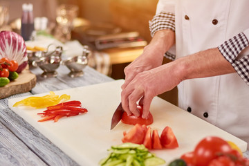 Chef slicing tomato on cutting board. Male chef hands cutting fresh vegetables for salad. Chef at work, kitchen.