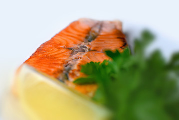 Grilled salmon fish steak with greens and lemon, isolated on white background. Menu photo.