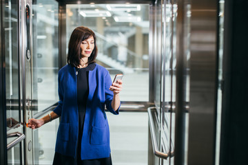 Businesswoman standing in office lobby, on mobile phone call, taking out personal organizer