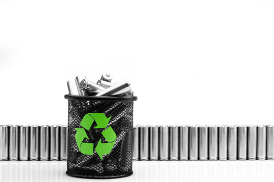 Ecology recycling concept, nature energy, used or new battery on recycle garbage bin, rechargeable AA accumulator, alkaline batteries in row on white background
