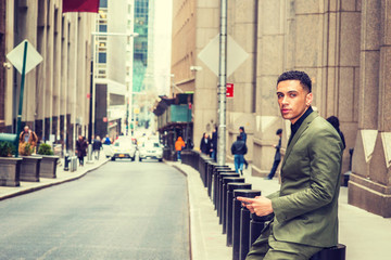 American Businessman traveling in New York, wearing green suit, black undershirt, sitting on pillar on vintage street, looking around, texting on cell phone. People, car on background. Filtered effect