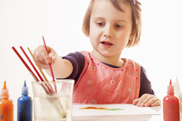 Сute little girl learns to paint as the most powerful investment in successful future. Creativity, education, success concept.