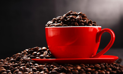 Composition with red cup of coffee and beans